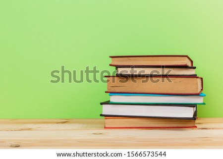 Simple Simple composition of many hardback books, unprocessed books on a wooden table and a green background. back to school. Copy space. Education. #1566573544