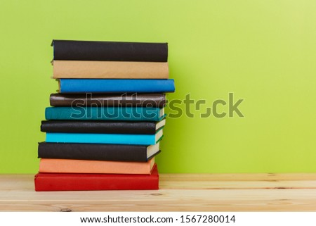 Simple Simple composition of many hardback books, unprocessed books on a wooden table and a green background. back to school. Copy space. Education. #1567280014