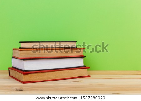 Simple Simple composition of many hardback books, unprocessed books on a wooden table and a green background. back to school. Copy space. Education. #1567280020