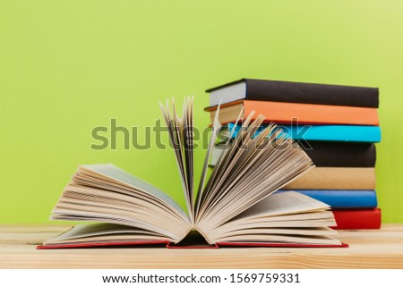 Simple Simple composition of many hardback books, unprocessed books on a wooden table and a green background. back to school. Copy space. Education. #1569759331