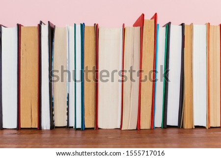 Simple Simple composition of many hardback books, unprocessed books on a wooden table and a pale pink background. back to school. Copy space Education. #1555717016
