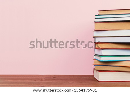 Simple Simple composition of many hardback books, unprocessed books on a wooden table and a pale pink background. back to school. Copy space Education. #1564195981