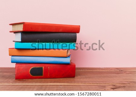 Simple Simple composition of many hardback books, unprocessed books on a wooden table and a pale pink background. back to school. Copy space Education. #1567280011