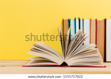 Simple Simple composition of many hardback books, unprocessed books on a wooden table and a yellow background. back to school. Copy space. Education. #1555717022