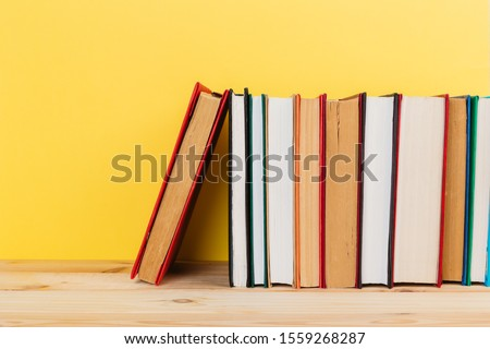 Simple Simple composition of many hardback books, unprocessed books on a wooden table and a yellow background. back to school. Copy space. Education. #1559268287