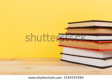 Simple Simple composition of many hardback books, unprocessed books on a wooden table and a yellow background. back to school. Copy space. Education. #1564195984