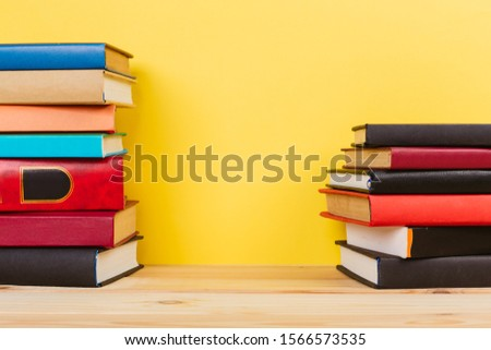 Simple Simple composition of many hardback books, unprocessed books on a wooden table and a yellow background. back to school. Copy space. Education. #1566573535