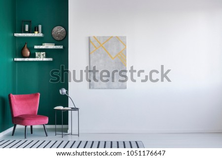 Simple sitting room interior with pink armchair, side table with lamp and painting on an empty wall #1051176647