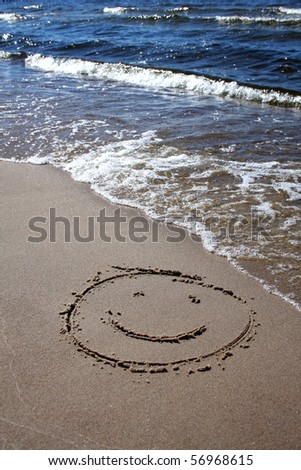 simple smile drawing in the sand on the beach