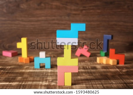 Simple solutions to complex problems. Strategy in business. Wooden Tetris cubes on a dark background as a puzzle symbol. The challenge with a difficult solution