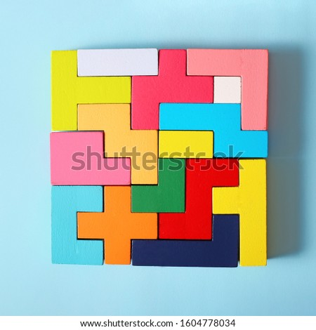 Simple solutions to decide problems. Strategy in business. Wooden Tetris cubes on a blue background as a puzzle symbol. The challenge with a difficult solution