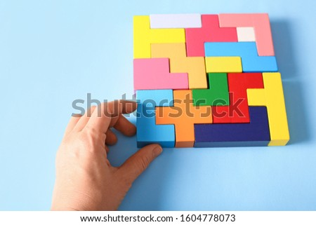 Simple solutions to solve problems. Strategy in business. Wooden tetris cubes in the hand on a blue background as a puzzle symbol. The challenge with a difficult solution