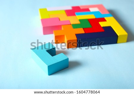 Simple solutions to solve problems. Strategy in business. Wooden Tetris cubes on a blue background as a puzzle symbol. The challenge with a difficult solution