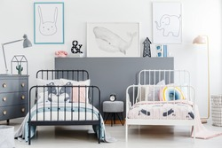 Simple style siblings bedroom interior with black and white beds. Rabbit, whale and elephant posters on white wall and gray drawer cabinet. Real photo