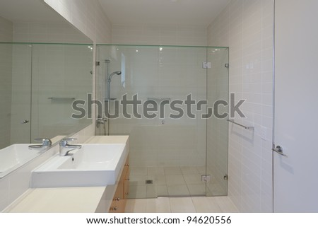 Simple stylish bathroom with shower, sink and mirror