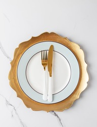 Simple table set with golden and white tableware on white marble. Gold fork and knife at white blue plate with gold dish