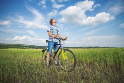 Simple teen boy on a bicycle in a summer field