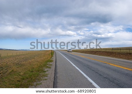 Simple view of a slightly curved road through a vast field near Kenosha Pass in Colorado, with a sheriff car on the road, and a mostly cloudy sky.