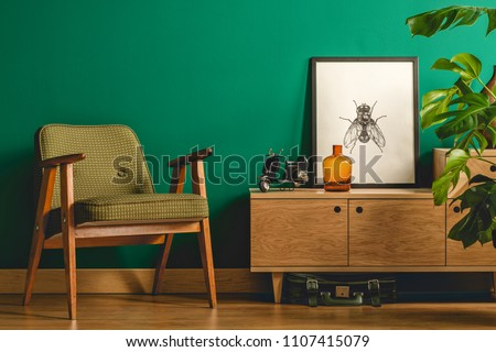 Simple vintage room interior with green walls, wooden floor, green chair, cupboard, poster and plant #1107415079