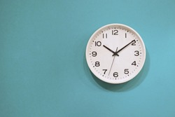Simple wall clock hanging on a blue wall