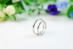 Simple wedding rings (bands) with blue flowers in the white background