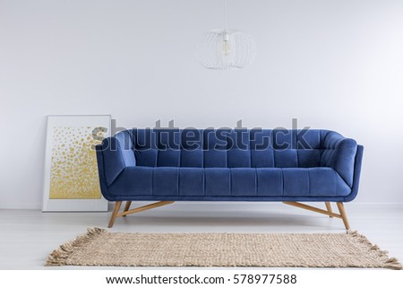 Simple white room with blue sofa and rug #578977588