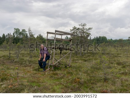 simple wooden hunting tower in the swamp, a man resting at the hunting tower, hiking in the swamp with snowshoes, traditional swamp plants, mire background, bog texture in summer