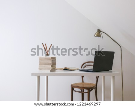 Simple workspace interior. Laptop computer, open book and a pile of books on a white modern desk. Empty white wall for copy space. #1221469297