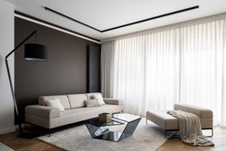 Simplicity and elegance in bright living room with big windows behind white curtains, big beige couch and seat, modern coffee table and black lamp