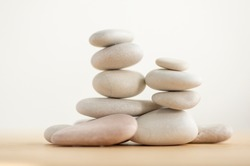 Simplicity stones cairns isolated on white background, group of light gray pebbles built in towers, wooden table, harmony and balance