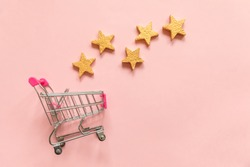 Simply flat lay design small supermarket grocery push cart for shopping and 5 gold stars rating isolated on pink pastel background. Retail consumer buying online assessment and review concept