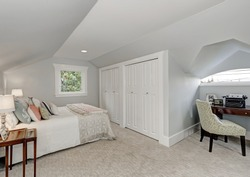 Simply furnished Attic bedroom interior, white doors closet and beige carpet floor. Small home office area with retro typing machine. Northwest, USA