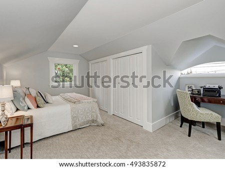Photo of Simply furnished Attic bedroom interior, white doors closet and beige carpet floor. Small home office area with retro typing machine. Northwest, USA