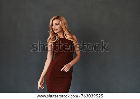 Simply stunning. Attractive young smiling woman in dress looking away while standing against grey background
