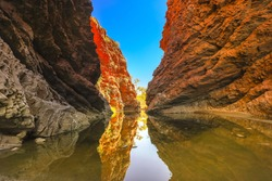 Simpsons Gap reflected in permanent waterhole in West MacDonnell National Park, Northern Territory near Alice Springs on Larapinta Trail in Central Australia. Popular landmark in Australian outback.