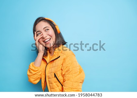 Sincere carefree Asian woman makes face palm smiles gladfully has fun while walking on street listens music via wireless headphones has happy mood models against blue wall with blank copy space Stock photo ©