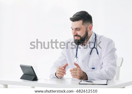 Sincere doctor is looking at camera of pc tablet and giving positive encouragement