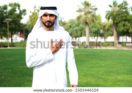 Sincere gesture by local Arab man while his hands on his heart  looking at the camera wearing Kandura