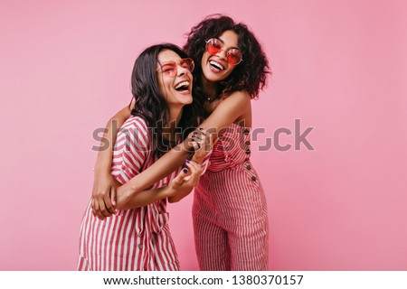 Sincere girls with radiant smile pose in striped pink overalls. Summer shot in studio of funny models