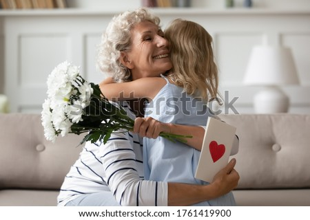 Sincere old grandma hugs small attentive granddaughter express her gratitude for received surprise at birthday or 8-march Woman Day. Grandchild makes surprise for granny gave her flowers and postcard
