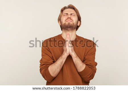 Sincere request to god. Portrait of imploring man with beard in sweatshirt praying up heartily, feeling guilty, pleading begging help from heaven. indoor studio shot isolated on gray background Foto stock ©