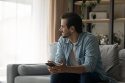 Sincere smiling dreamy young man in eyeglasses sitting on sofa with cellphone in hands, looking in distance thinking on received message with good news, feeling joyful resting alone in living room.