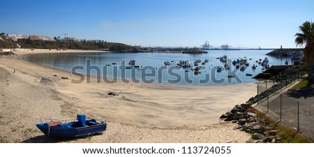 Sines beach bay and traditional fishing harbour. Industrial harbour in the horizon. Portugal. - stock photo