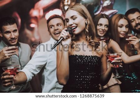 Sing and Drink. Black Dress. Trendy Nightclub. Have Fun. Background. Cheerful. Smiling Girl. Singing Songs. Handsome Men. Beautiful Girls. Friends at Karaoke Club. Karaoke Club. Celebration.