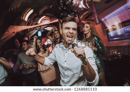 Sing in Karaoke. Men. Karaoke Club. Have Fun. Great Mood. Celebration. Dance Club. Holidays Concept. Dancing People. Young People. Sing.Microphone. Trendy Modern Nightclub. Party Maker. Birthday. Men.