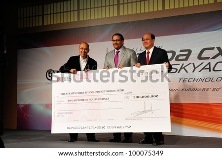 SINGAPORE - APRIL 13: Karsono Kwee, Exec Chairman of Eurokars, presenting Pocket Money Fund cheque to Mr Han Fook Kwang at the launch of new Mazda CX-5 crossover SUV April 13, 2012 in Singapore