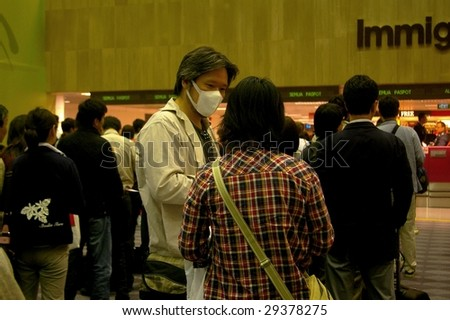 SINGAPORE - APRIL 29 : Passengers waiting in line at Singapore International Airport. Some passengers wearing face masks, because of the outbreak of Swine flu. April 29, 2009 Changi airport, Singapore