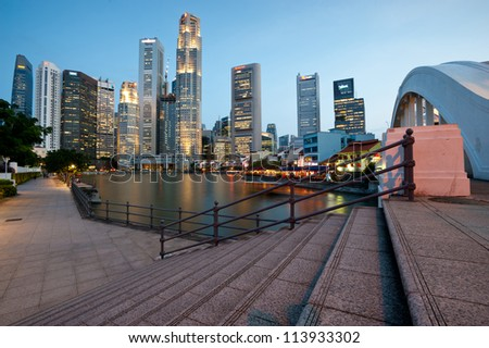 SINGAPORE - APRIL 25:The Singapore skyline shines at night as tourists frequent the riverside shops and restaurants along Boat Quay, Singapore.April 25, 2011 in Singapore