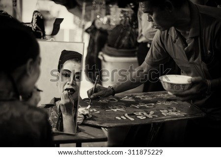 SINGAPORE - AUG 20: Dark sepia version of Chinese Teochew opera singer makeup and man writing the programme for the day on Aug 20, 2015 in SINGAPORE.