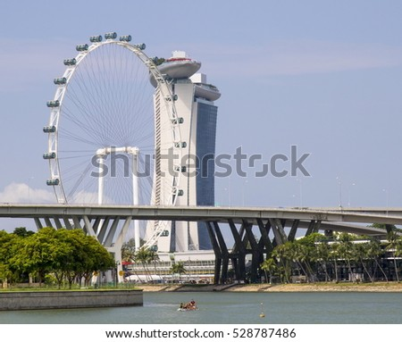 SINGAPORE - AUGUST 10, 2016. Ferris wheel, Marina Bay Sands Hotel and boat with men paddling on the river
